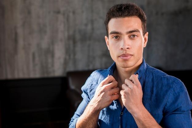 Portret van een kraag van de jonge mensenholding van zijn overhemd die camera bekijken