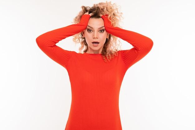 Portret van een krullend blond meisje in een rode jurk