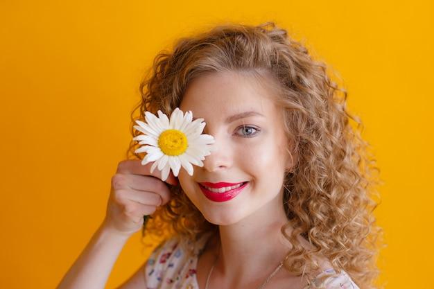 Portret van een krullend meisje met een madeliefje in haar haar op geel