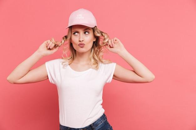 Portret van een krullende blonde vrouw met een casual t-shirt en een pet die aan de voorkant glimlacht, geïsoleerd over roze muur