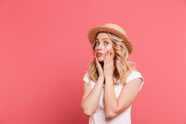 Portret van een krullende blonde vrouw met een strohoed die naar de voorkant kijkt met verrassing geïsoleerd over roze muur