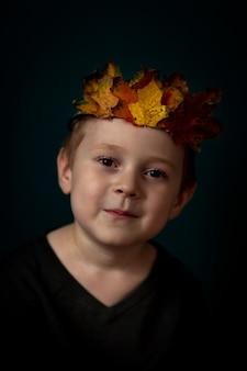 Portret van een lachend 4-6 kind met een kroon van bladeren op zijn hoofd