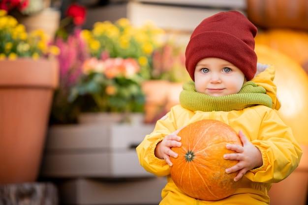 Portret van een lachend kind in een felgele overall met een oranje pompoen in zijn handen op de herfstbeurs.