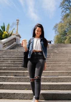 Portret van een lachend meisje dat een kopje draagt