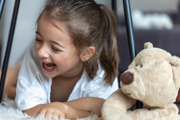Portret van een lachend meisje in de buurt van een teddybeer thuis.