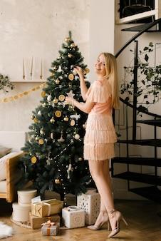 Portret van een lachend meisje in een roze jurk siert de kerstboom en het nieuwe jaar