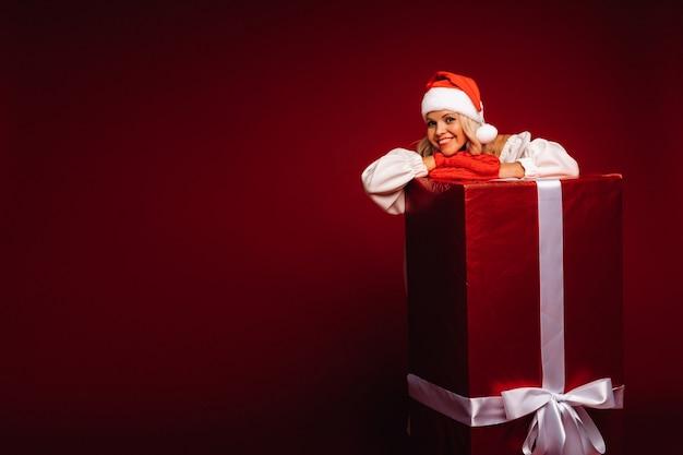 Portret van een lachend meisje in een witte jurk en kerstmuts met een enorm kerstcadeau op een rode achtergrond.