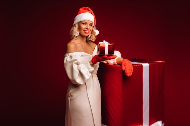 Portret van een lachend meisje in een witte jurk en kerstmuts met een kerstcadeau op een rode achtergrond.