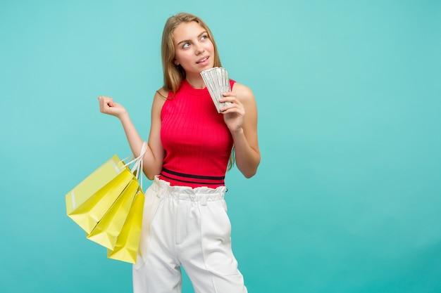 Portret van een lachend meisje met boodschappentassen en een heleboel geld vs bankbiljetten geïsoleerd op blauwe achtergrond black friday concept