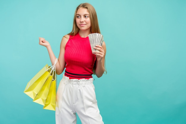 Portret van een lachend meisje met boodschappentassen en een heleboel geld vs-bankbiljetten geïsoleerd op blauwe achtergrond. black friday-concept