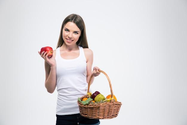 Portret van een lachend meisje met een mand met geïsoleerd fruit