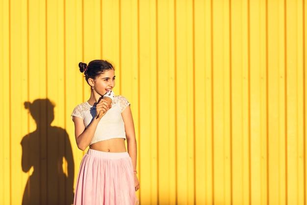 Portret van een lachend meisje met ijs in handen op een gele zomer achtergrond. trendy meisje met plezier.