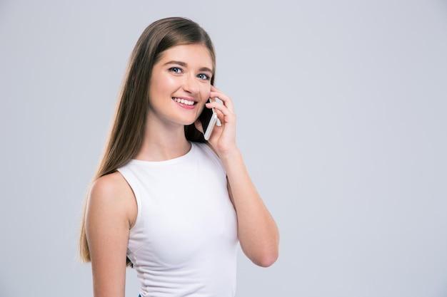 Portret van een lachend meisje praten aan de telefoon geïsoleerd