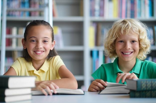 Portret van een lachend, mooi donkerharig schoolmeisje en een schattige schooljongen die aan de tafel zit en vooruit kijkt