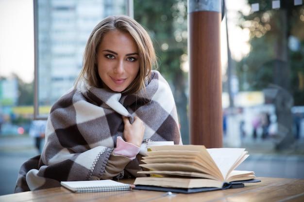 Portret van een lachend mooi meisje dat aan tafel zit met een boek en koffie
