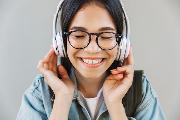 Portret van een lachend mooi meisje in een spijkerjasje met een bril die over een grijze muur wordt geïsoleerd en muziek luistert met een koptelefoon.