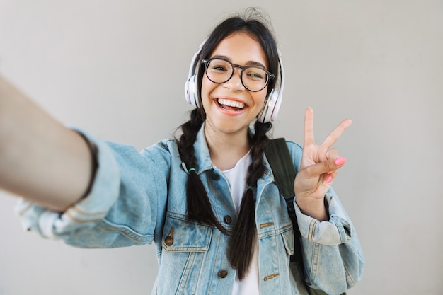 Portret van een lachend mooi meisje in een spijkerjasje met een bril geïsoleerd over een grijze muur die muziek luistert met een koptelefoon en een selfie maakt met een camera die vredesgebaar toont.