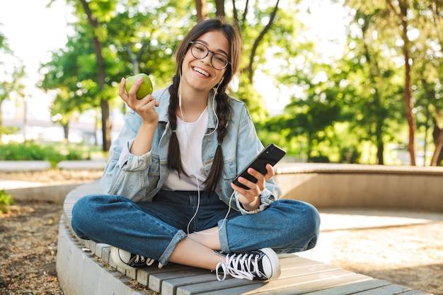 Portret van een lachend positief schattig jong studentenmeisje met een bril die buiten op een bankje zit in het natuurpark met behulp van een mobiele telefoon die luistert naar muziek met een koptelefoon die een appel vasthoudt.
