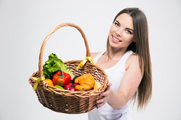 Portret van een lachend schattig meisje dat mand met fruit geeft op de camera geïsoleerd