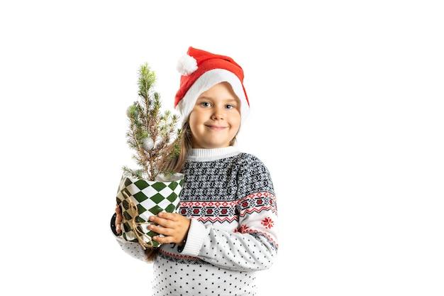 Portret van een lachend schattig meisje in een witte kersttrui met rendieren en een kerstman hoed hol...