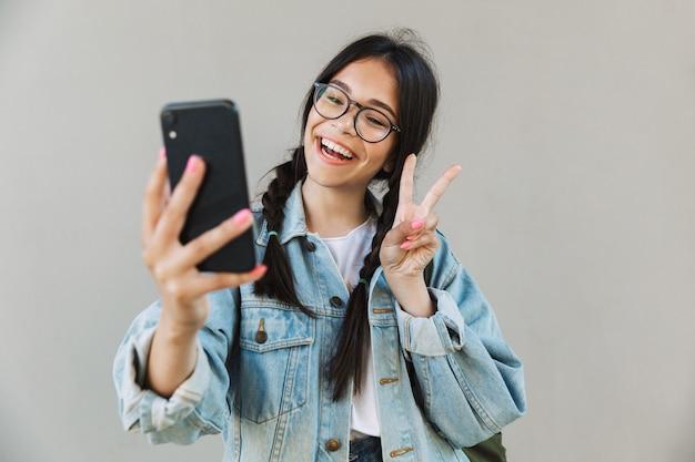 Portret van een lachend schattig mooi meisje in spijkerjasje met bril geïsoleerd over grijze muur met behulp van mobiele telefoon, neem een selfie die vrede toont.