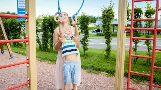 Portret van een lachende 3 jaar oude kleine jongen die pull-ups doet aan ringen op een sportplein terwijl moeder hem vasthoudt en ondersteunt