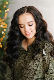 Portret van een lachende aantrekkelijke brunette met professionele make-up met haar ogen dicht