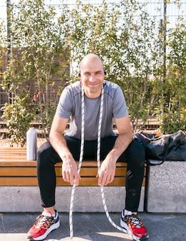 Portret van een lachende atleet man met touw rond zijn nek zittend op bankje met waterfles en tas