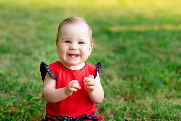 Portret van een lachende baby in de zomer op het groene gras in een rode bodysuit die geniet van de frisse lucht, close-up, ruimte voor tekst
