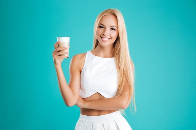 Portret van een lachende blonde vrouw die naar de camera kijkt en koffie drinkt om te gaan geïsoleerd op de blauwe achtergrond
