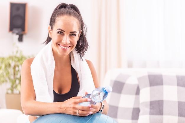 Portret van een lachende brunette met een witte handdoek om haar nek na het sporten