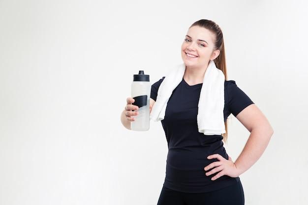 Portret van een lachende dikke vrouw in sportkleding met shaker geïsoleerd op een witte muur