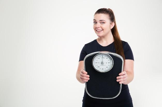 Portret van een lachende dikke vrouw met een weegmachine geïsoleerd op een witte muur