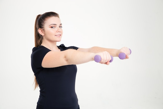 Portret van een lachende dikke vrouw training met halters geïsoleerd op een witte muur