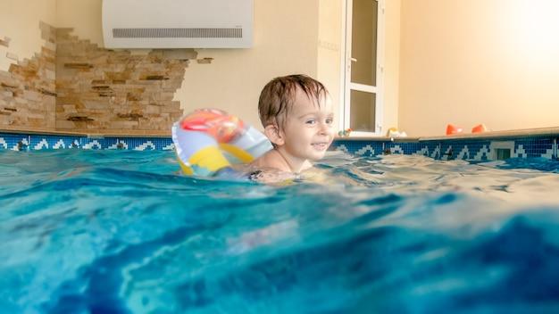 Portret van een lachende en lachende 3 jaar oude kleine jongen die zwemt met een opblaasbare kleurrijke ring en speelt met een strandbal in het zwembad