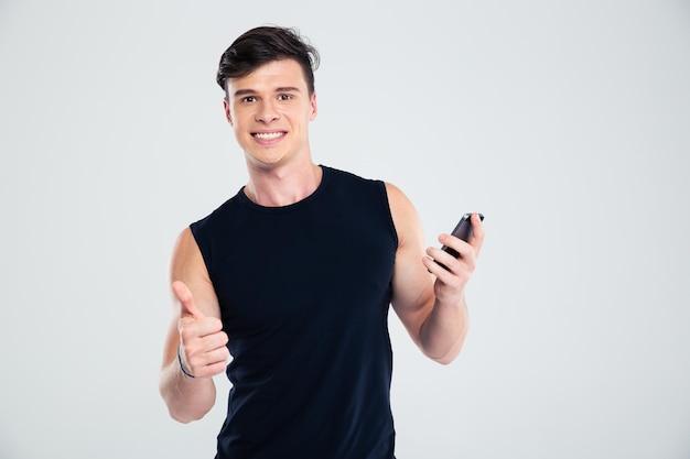 Portret van een lachende fitnessman die smartphone vasthoudt en duim omhoog laat zien
