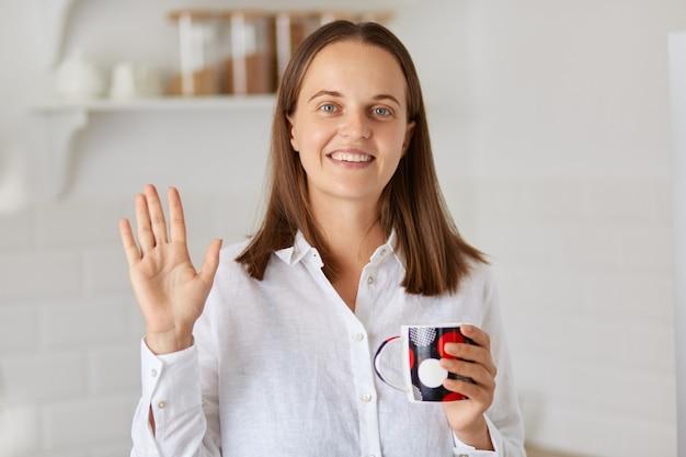 Portret van een lachende gelukkige jonge volwassen vrouw met een wit overhemd die naar de camera kijkt en met de hand zwaait, groet, hallo zegt, positieve emoties uitdrukt.