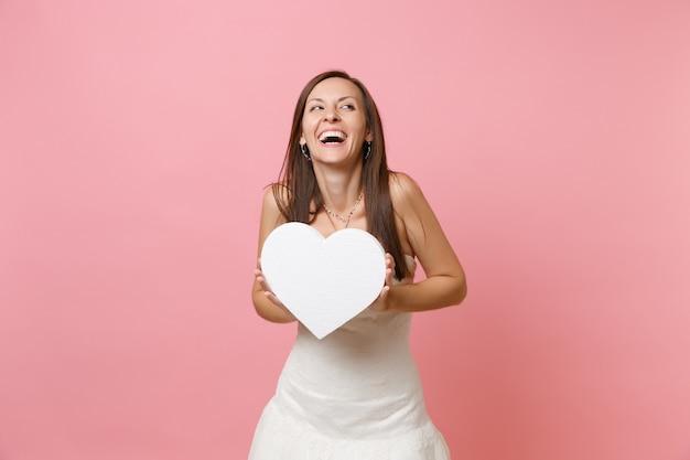 Portret van een lachende gelukkige vrouw in een mooie witte jurk die een wit hart vasthoudt met kopieerruimte