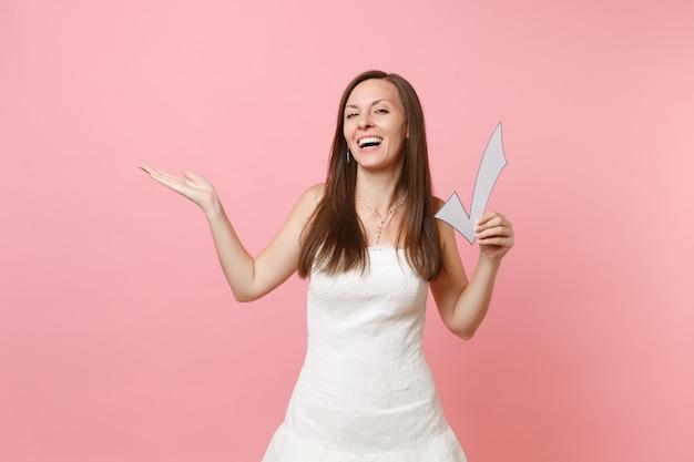 Portret van een lachende gelukkige vrouw in een witte jurk die met de hand opzij wijst, met een vinkje,