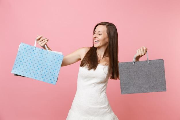 Portret van een lachende gelukkige vrouw in een witte jurk die na het winkelen op veelkleurige pakketten met aankopen kijkt