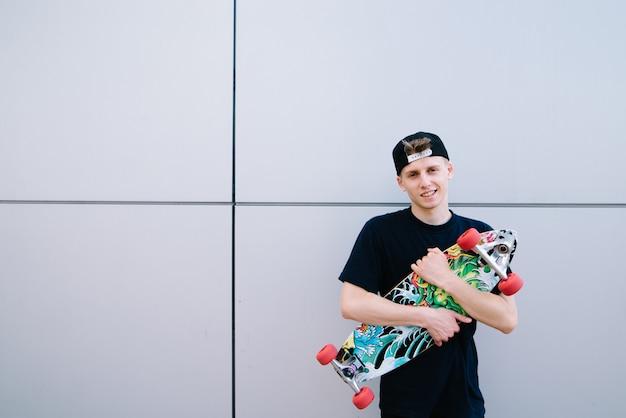 Portret van een lachende hipster met een longboard in zijn handen tegen een grijze muur. jonge man met een skateboard vormt op een grijs