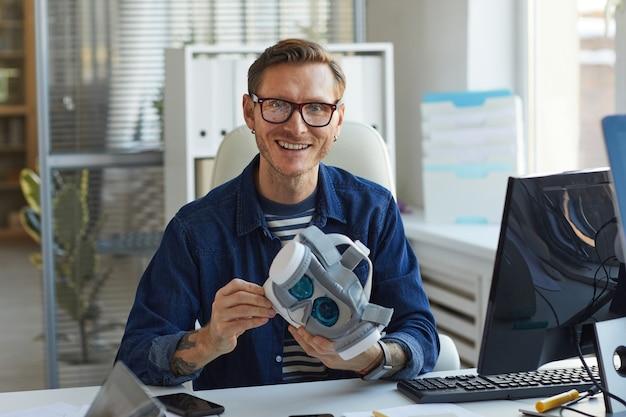 Portret van een lachende it-ontwikkelaar die een vr-headset vasthoudt en naar de camera kijkt terwijl hij aan augmenter reality-toepassingen werkt, kopieer ruimte