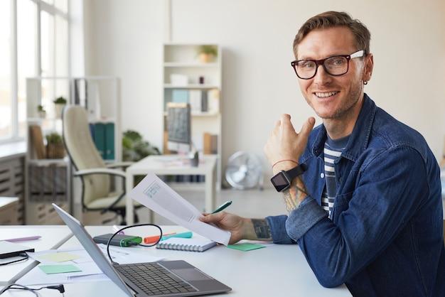 Portret van een lachende it-ontwikkelaar die naar de camera kijkt tijdens het ontwerpen van een interface voor een mobiele applicatie of website, kopieer ruimte