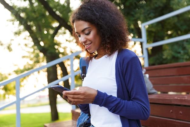Portret van een lachende jonge afrikaanse meisje met rugzak met behulp van mobiele telefoon tijdens het rusten in het park