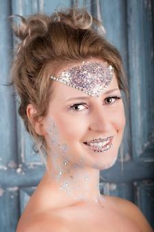 Portret van een lachende jonge blonde vrouw met bruine ogen, gekleurde make-up en sparkles