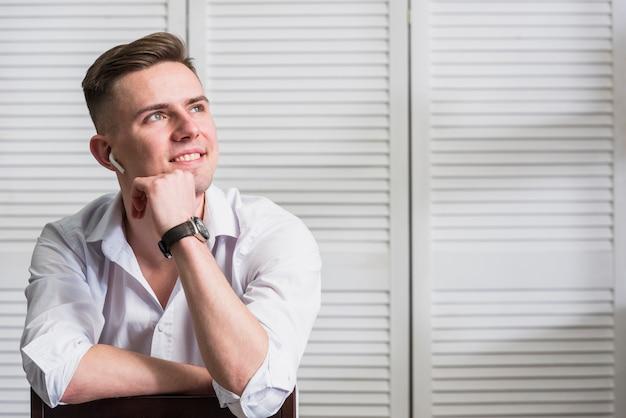 Portret van een lachende jonge man met draadloze oortelefoon in zijn oor wegkijken