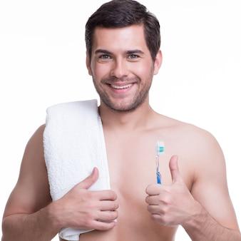 Portret van een lachende jonge man met een tandenborstel - geïsoleerd op wit.