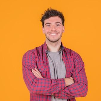 Portret van een lachende jonge man met zijn arm gekruist staande tegen een oranje achtergrond