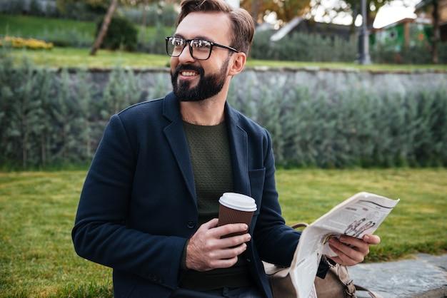 Portret van een lachende jonge man zit met een krant