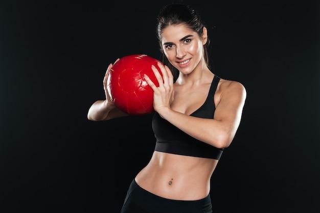 Portret van een lachende jonge sportvrouw met fitnessbal over zwarte muur